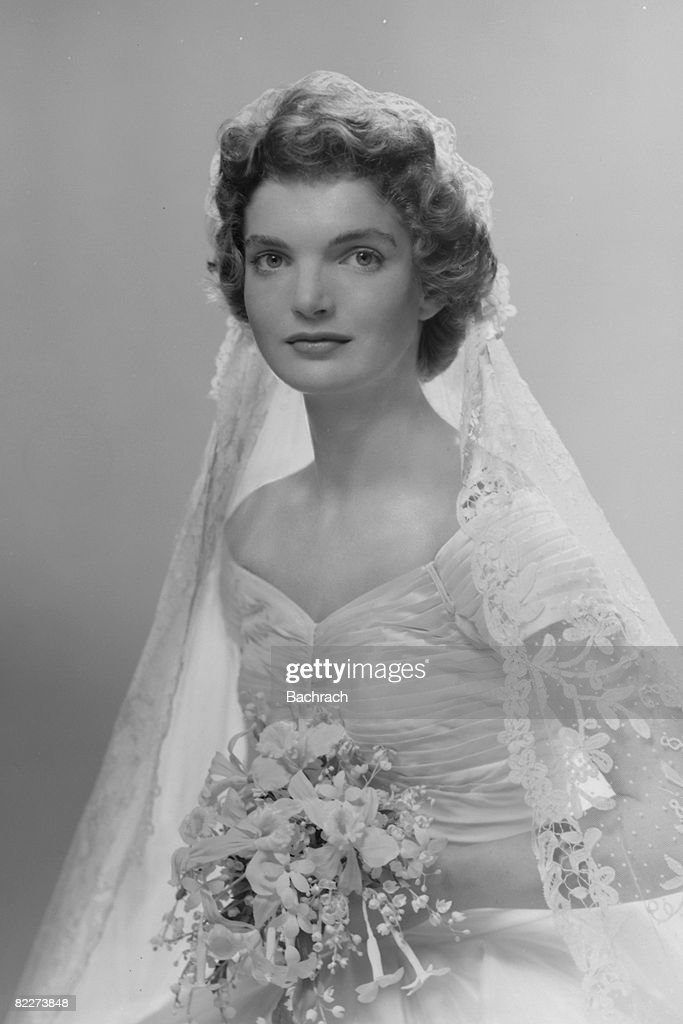 Bridal portrait of Jacqueline Lee Bouvier (1929 - 1994) shows her in an Anne Lowe-designed wedding dress, a bouquet of flowers in her hands, New York, New York, 1953.
