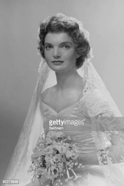 Bridal portrait of Jacqueline Lee Bouvier shows her in an Anne Lowedesigned wedding dress a bouquet of flowers in her hands New York New York 1953