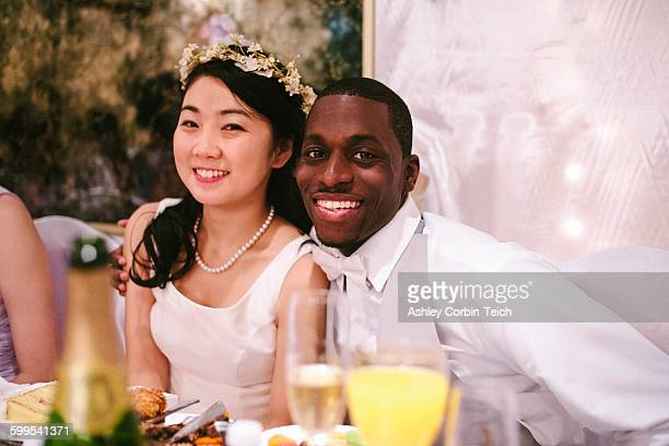 Bride and bridegroom at wedding reception sitting side by side looking at camera smiling