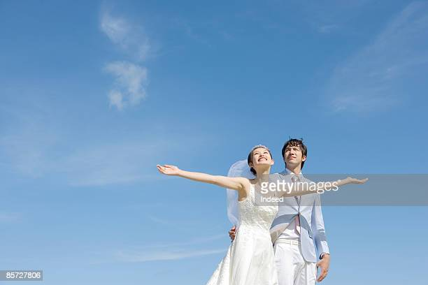 Bride and bridegroom looking up to sky