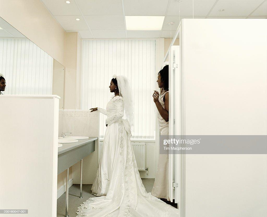 Bride And Bridesmaid Facing Mirror In Bathroom Stock Photo