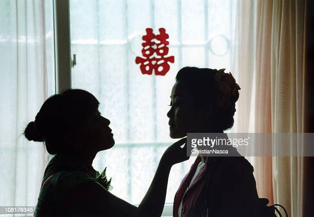 Bride and bridesmaid getting ready for a Chinese wedding.