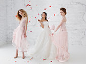Bride and bridesmaids dancing in white studio with flying petals. Full-lenght portrait