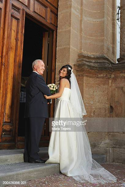 Bride and father entering church, smiling