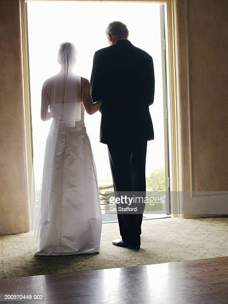 Bride and father standing by doorway, rear view