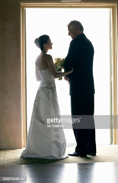Bride and father standing in doorway