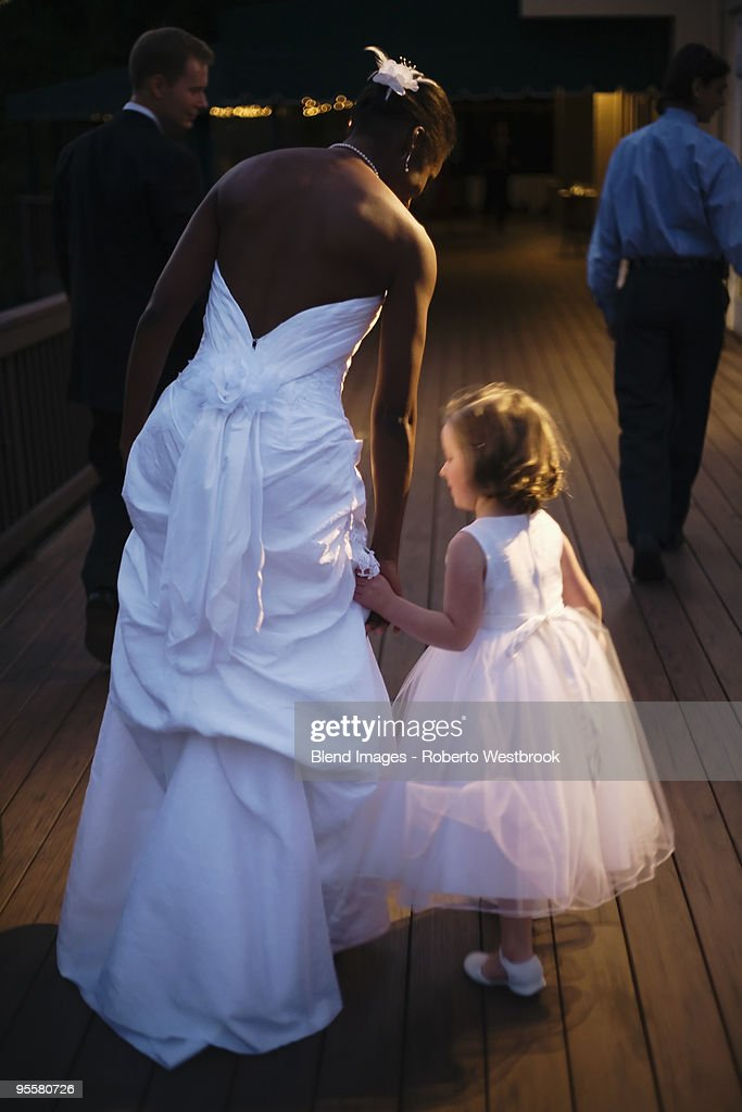 Bride and flower girl holding hands : Stock Photo