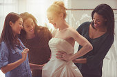 Bride and friends shopping for wedding gown