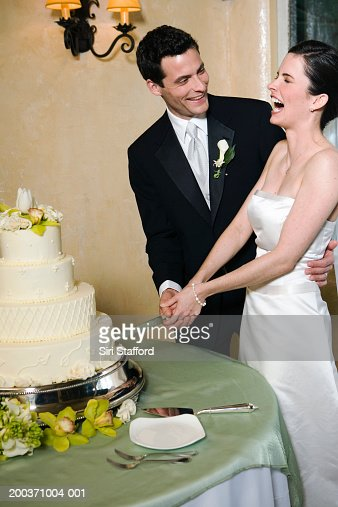 Bride and groom about to cut wedding cake, bride laughing : Stock Photo