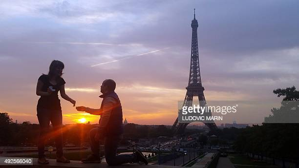 A bride and groom are photographed at the Trocadero Plaza opposite the Eiffel tower at sunrise on October 12 2015 in Pairs AFP PHOTO / LUDOVIC MARIN