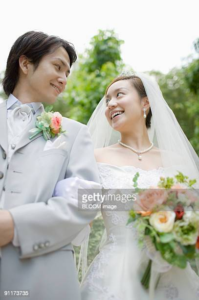 Bride and groom, arm in arm, smiling at each other