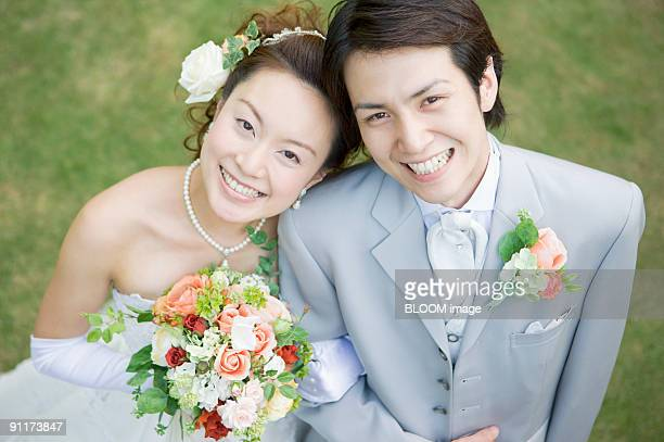 Bride and groom arm in arm, smiling, high angle view, portrait