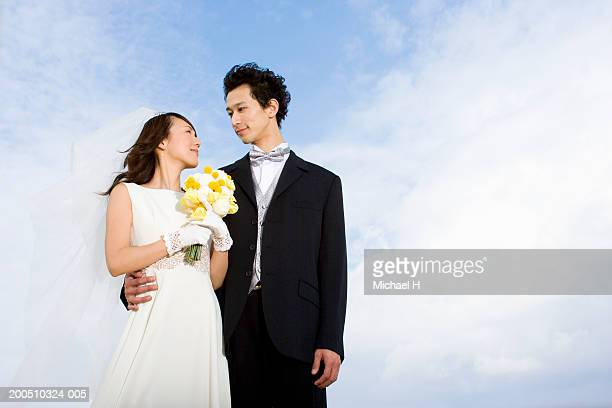 Bride and groom, bride holding bouquet of flowers, outdoors