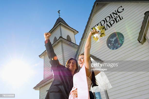 Bride and groom by wedding chapel