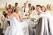 Bride And Groom Celebrating With Guests At Reception Smiling To Camera