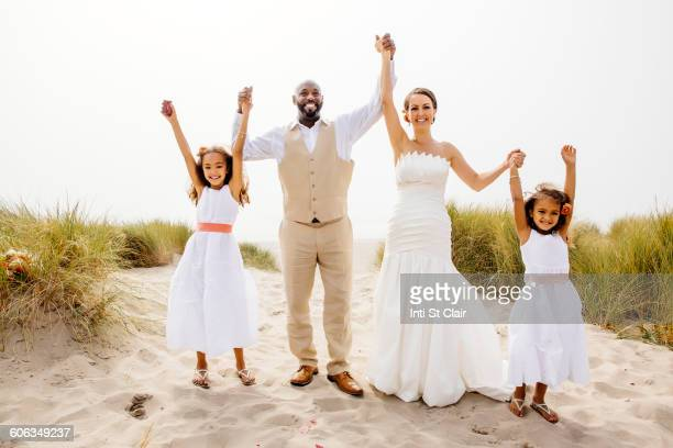 Bride and groom cheering with flower girl daughters