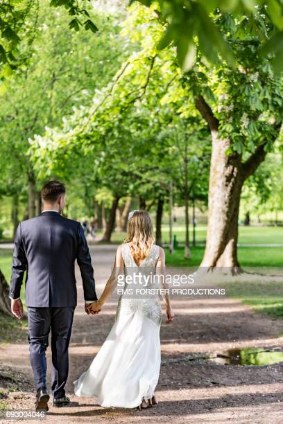 bride and groom couple in wedding suit and white wedding dress seen from behind walking hand in hand through a park with green trees