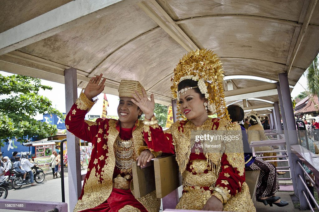Bride and groom couple wave during a mass wedding ceremony on December 12, 2012 in Yogyakarta, Indonesia. Twelve couples participated in a mass wedding as today saw a surge in marriage across the globe to mark the once in a century date of 12/12/12.