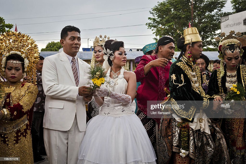 Bride and groom couples celebrate their marriage during a mass wedding ceremony on December 12, 2012 in Yogyakarta, Indonesia. Twelve couples participated in a mass wedding as today saw a surge in marriage across the globe to mark the once in a century date of 12/12/12.