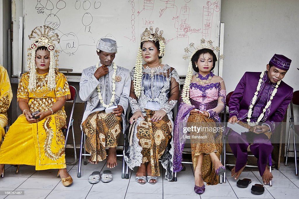 Bride and groom couples prepare for marriage during a mass wedding ceremony on December 12, 2012 in Yogyakarta, Indonesia. Twelve couples participated in a mass wedding as today saw a surge in marriage across the globe to mark the once in a century date of 12/12/12.