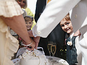 'Bride and groom cutting wedding cake, boy (6-7) smiling, portrait'