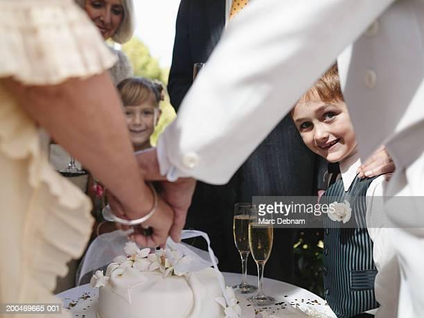 'Bride and groom cutting wedding cake, boy (6-7) smiling, portrait'