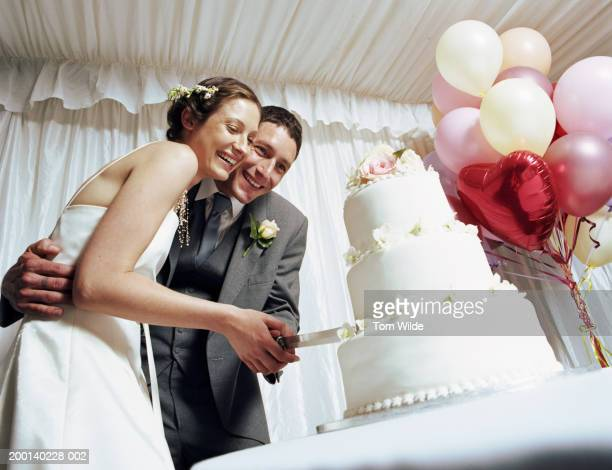 Bride and groom cutting wedding cake in marquee, low angle view