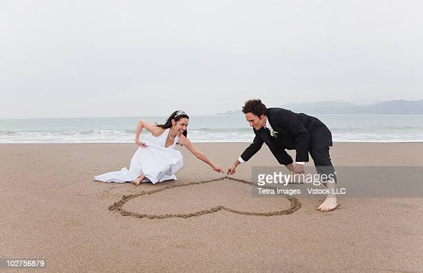 Bride and groom drawing a heart in the sand