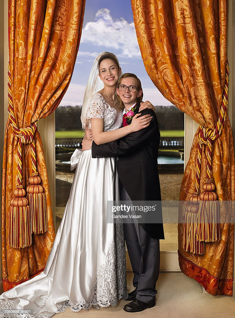 Bride and groom embracing in front of window, smiling, portrait : Stock Photo