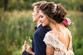 Happy bride and groom embracing in the park, wedding day