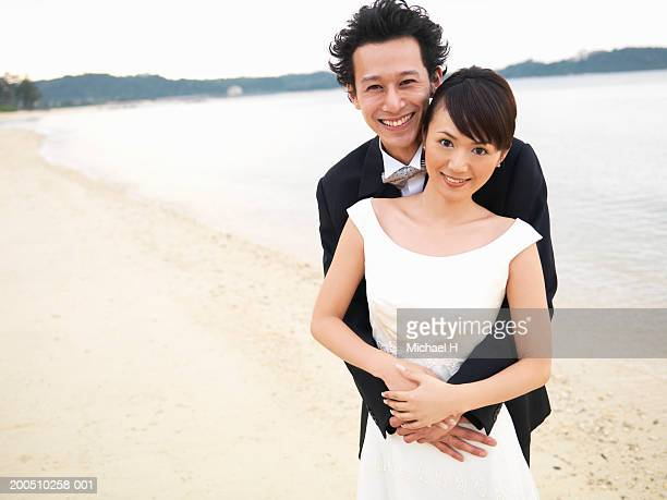 Bride and groom embracing on beach, smiling, portrait