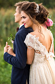 Bride and groom embracing in the park, view side, summertime