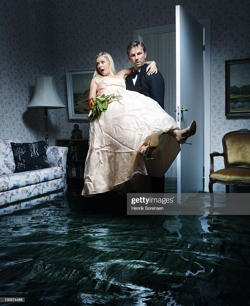 bride and groom entering flooded room : Stock Photo