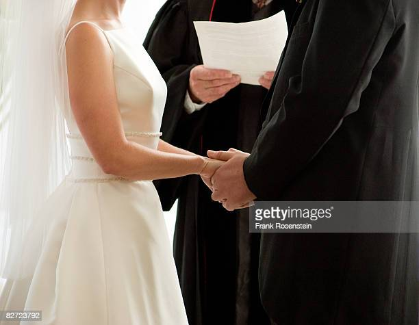 Bride and groom exchange vows holding hands