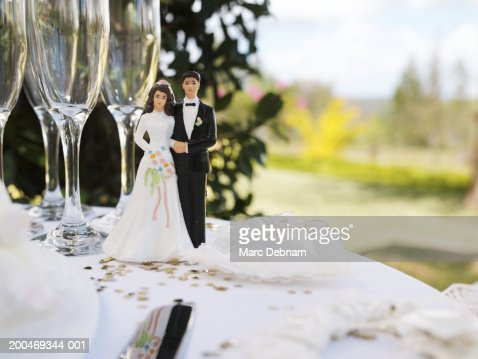 Bride and groom figurine on table by champagne flutes : Stock Photo