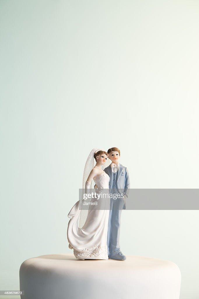 Bride and groom figurines on top of wedding cake