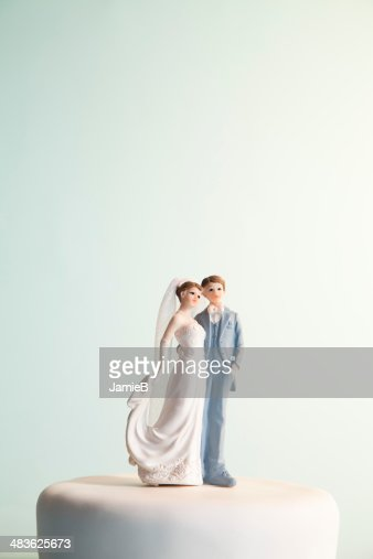 Bride and groom figurines on top of wedding cake