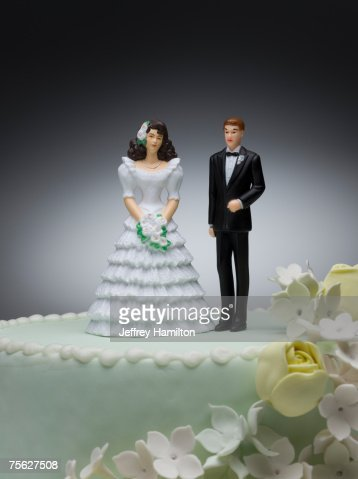 Bride and groom figurines on top of wedding cake : Stock Photo