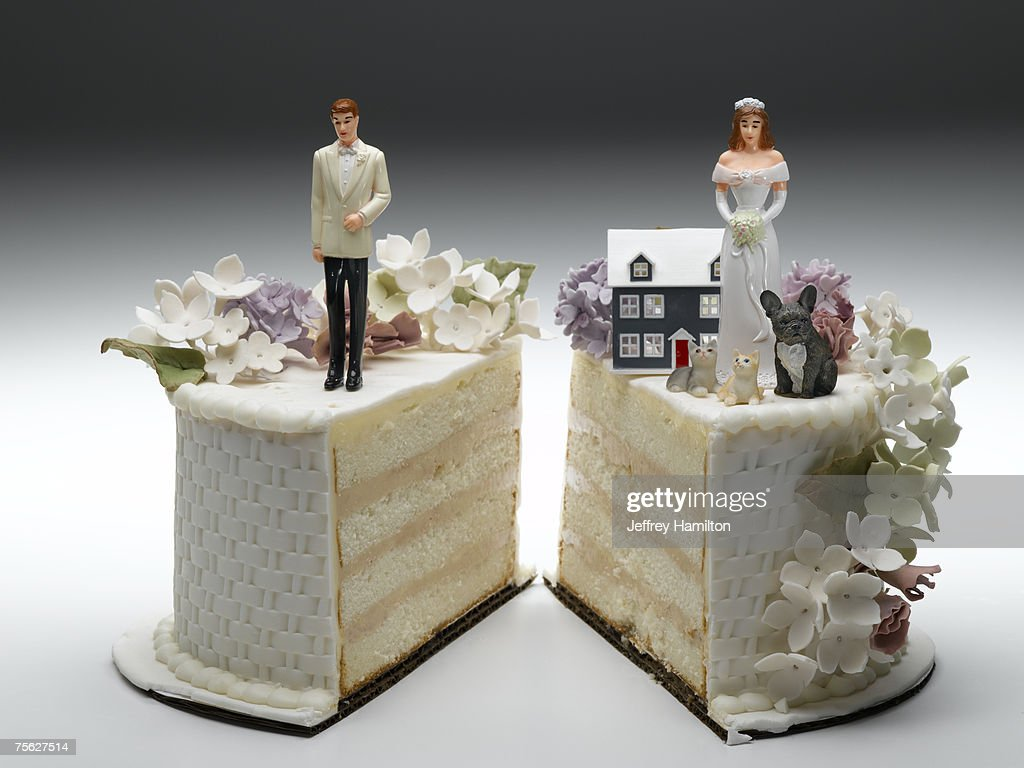 Bride and groom figurines standing on two separated slices of wedding cake : Stock Photo
