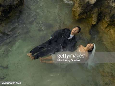 Bride and groom floating in tidal pool, elevated view : Stock Photo