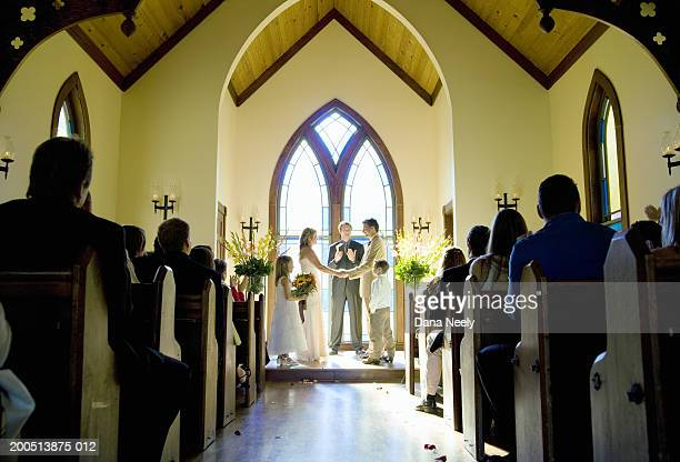 Bride and groom getting married during wedding ceremony in chapel