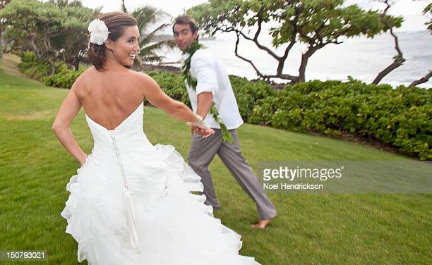 A bride and groom hold hands and walk together