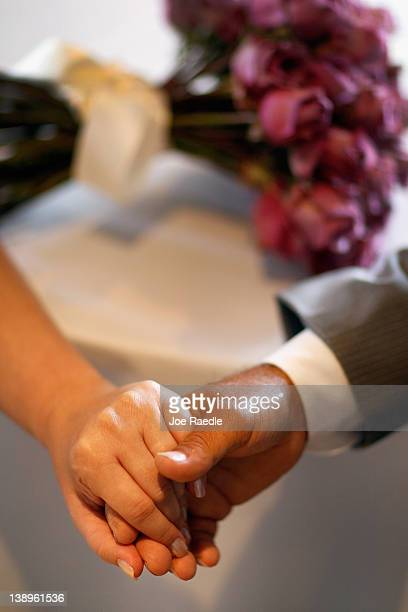 A bride and groom hold hands during a group Valentine's day wedding ceremony at the National Croquet Center on February 14 2012 in West Palm Beach...