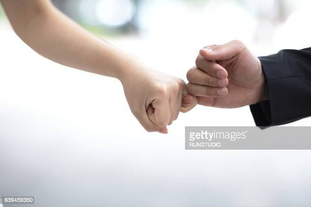 bride and groom hold little fingers