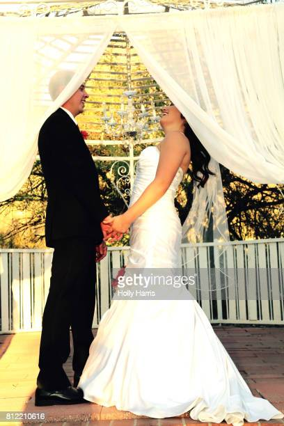 Bride and groom holding hands in a gazebo laughing, faces behind curtains