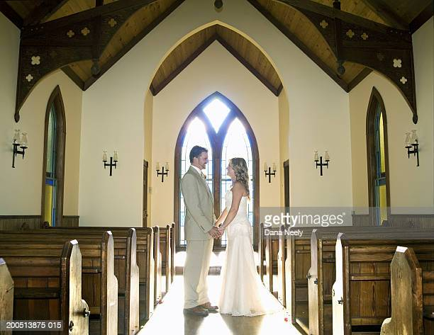 Bride and groom holding hands in chapel, side view