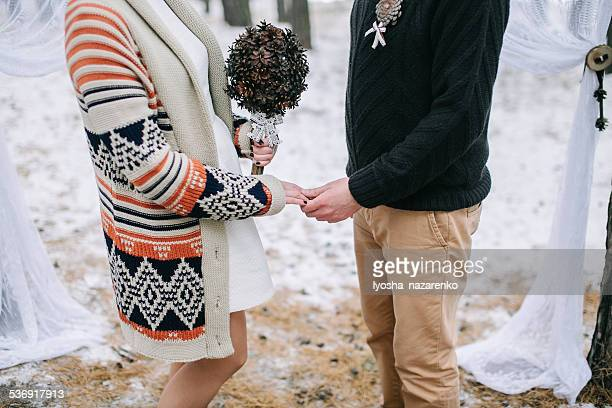 Bride and groom holding hands during the winter wedding ceremony