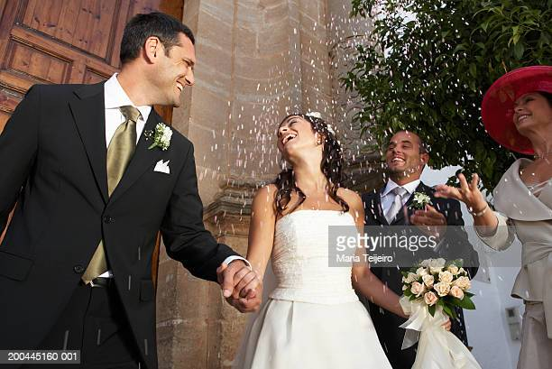 Bride and groom holding hands, surrounded by falling confetti,laughing