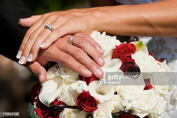 Braut und Bräutigam halten Hände und Ringe auf Blumen-Strauß