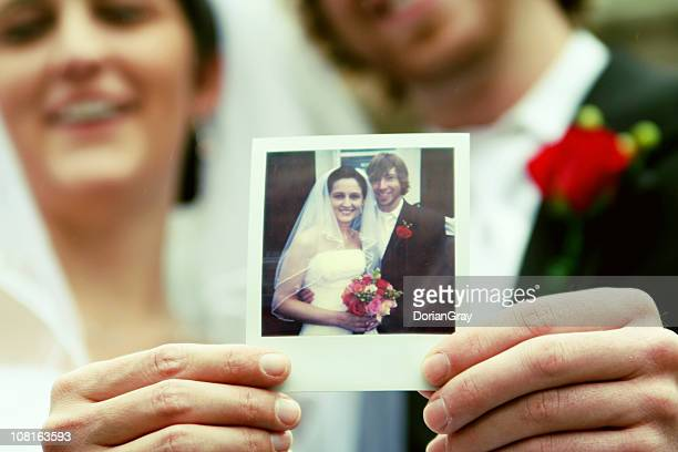 Bride and Groom Holding Photograph of Themselves